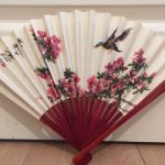 Open paper fan with red wooden handle and decorated with cherry blossom and a bird