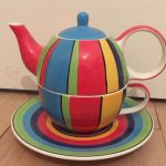 Brightly coloured, striped teapot, cup and saucer