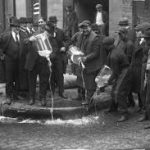Two men pour alcohol out of glass jars and into the gutter, watched by a group of men. All are wearing suits and flat caps