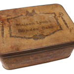 A brown tin, stamped Maison Lyons Dundee Cake
