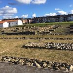 Stone foundations in a field surrounded by houses at Arbeia Roman fort