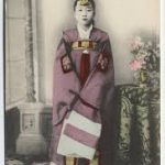 A hand-tinted photo of a Korean woman in traditional dress, standing beside a table with a vase of flowers on it.