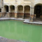 A green Roman bath, surrounded by arched doorways