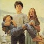 A teenage boy holding a small boy in his arms, with a girl standing behind them
