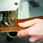 A hand pushing a piece of leather through a sewing machine