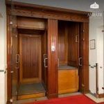 A wooden paternoster lift, showing both compartments