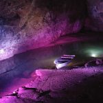 A small rowing boat sits on an underground river in a pink-lit cave