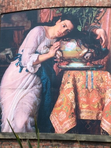 A woman in a pink nightgown rests her head on a round pot, her black her flowing over it.