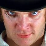 Malcolm McDowell as Alex in the film version of A Clockwork Orange. He wears a black bowler hat and white shirt