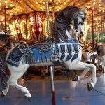 A blue-saddled, white carousel horse with black mane. The ride behind it is lit up with yellow bulbs
