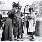 Two well-dressed women examine a young girl in an apron at a Victorian hiring fair