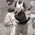 German athlete Kathrine Switzer is attacked by a race official in a black jacket as she's running the Boston Marathon
