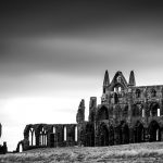 A black and white photo of the ruins of Whitby Abbey
