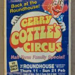 A poster advertising Gerry Cottle's Circus, which is written in large yellow letters on a circle. A red-haired, laughing clown is holding the circle.