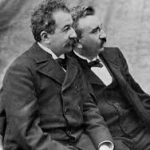 A black and white photo of the Lumiere brothers. The two men are seated, facing away from the camera. They both have curly hair and moustaches, and the man furthest from the camera wears glasses. They are both wearing Victorian coats and bow ties