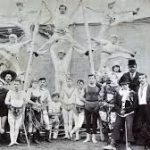 A black & white photo of 19th century circus performers. Acrobats in white suits stand above a group of their colleagues