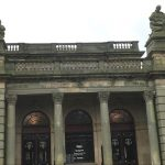 The grey stone front of the Shipley Art Gallery, with three arched doorways and two statues on the roof