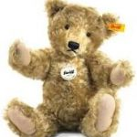 A jointed Steiff bear, sitting with arms raised. It has a yellow tag in its ear and a white badge on its chest