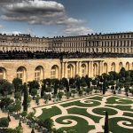 A blue, cloudy sky looms over the Palace of Versailles and its grounds