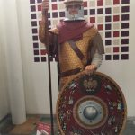 A Roman solider, wearing yellow tunic, red cloak, helmet and holding a spear and red, decorated shield