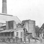 A blaack and white photo showing a group of men in front a colliery building with a tall chimney
